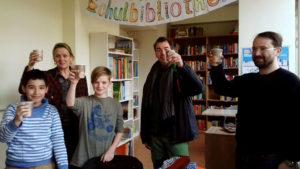 Die Sieger*innen und Platzierten stoßen mit Frau Helm, Boris Pfeiffer, Herrn Peter und den Lesepat*innen auf die Eröffnung der Schulbibliothek an.